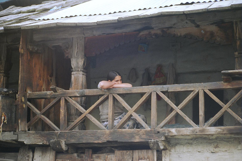 A young girl sitting in the balcony of her home.  Lost in deep thought.  What are her worries? Who is she waiting for? Does she know or care of what is happening elsewhere?