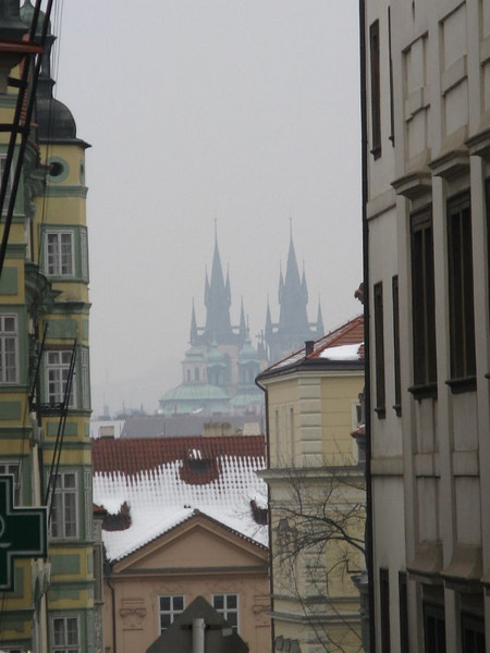 Nerudova Street in Malá Strana and the distant misty spires of the cathedral of Our Lady before Týn in Old Town