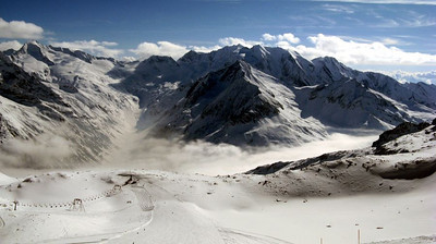 Southern view from Gefrorene Wand to Italy. The Schlegeiss chairlift is in the foreground, the Schlegeisspeicher lake and power station are in the valley below.  Hochfeiler/Gran Pilastro (3510 m) is the peak to the right of the lake; Großer Möseler/Grande Mèsule (3486 m) is to the left.