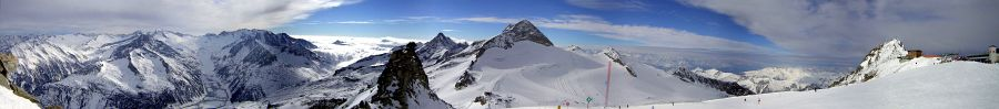 180-degree panoramic view from the top of the Hintertux Ski Area looking west, showing Italian Alps to the left and Zillertal Alps to the right, with Bavarian Alps in the background.