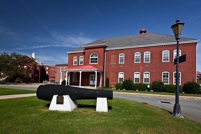 The old Garrison Headquarters  building, framed with a historic 10 inch Rodman Gun at Fort Monroe, Virginia.