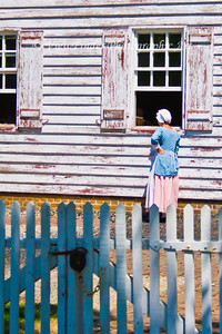 Colonial Williamsburg woman visits neighbor at the window.
