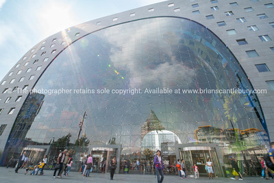 Rotterdam Market Hall in city, modern structure with rounded roof profile and interior painted ceiling mural.