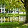 Urban building reflected in calm water of canal running through city under large leafy tree