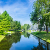 Urban building and leafy trees idyllicaly reflected in calm water of canal running through city under large leafy tree