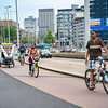 People cycling and walking along urban pavement surrounded by city commercial buildings.