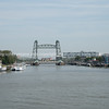 Rotterdam Netherlands - August 23 2017;  Mass River flowing through city under landmark De Hef lift bridge with boats moored along sides.