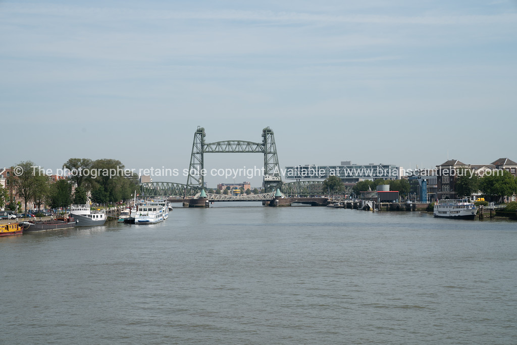 Harbor lined on both sides by wharves, mooring and buildings with steel railroad bridge known as De Hef
