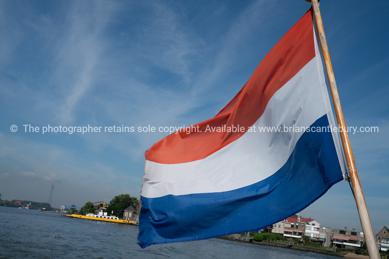 Dutch red, white and blue striped flag in breeze on stern of boat