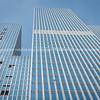 Blue toned facade of city high-rise office block from street below, De Rotterdam Building facade towering toward sky