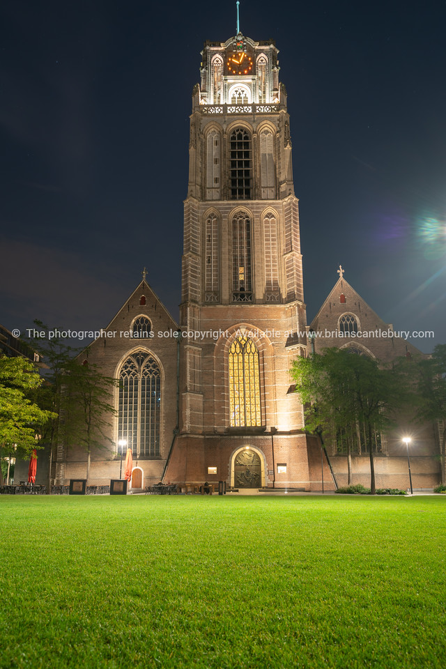 Gothic Saint Lawrence Church contrasts with bright green lawn at night long exposure
