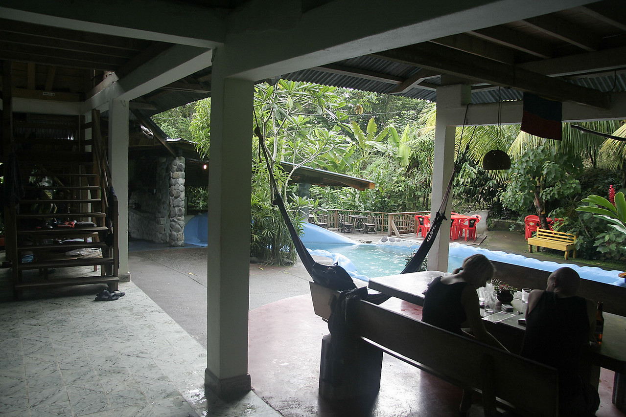 The view of the dining table, hammock, stream-fed pool and bar.