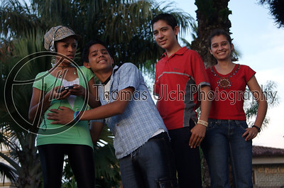 These kids are part of the dance troupe. I like how the two on the right smiling and friendly, the guy in the middle is maybe a little too friendly and the girl in green just wants to be left alone. It is almost as if she is saying... Ruinas de Copan, Honduras.