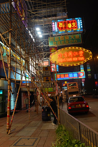 Bamboo scaffolding competes with neon signs for attention over the sidewalks.