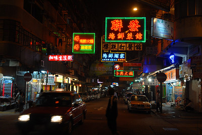 Hong Kong streets at night... neon signs rule the spaces above the streets.  Taxis prowl like sharks on the outer edge of the reef.