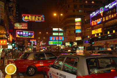 Hong Kong streets at night... neon signs rule the spaces above the streets.