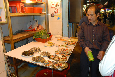 The proprietor of a sidewalk seafood cafe displays the creatures available for consumption.