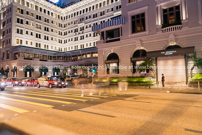 KOWLOON, HONG KONG - SEPTEMBER 19 2017; Long exposure night scene  pedestrian crossing with blurred people waiting in front of The Peninsula hotel and shops.