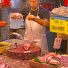 Fish monger weighting fish in HK market