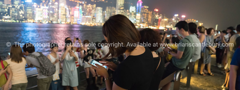 Tourists gather along Walk od Stars to view and take selfie of Victoria Harbor and comercial skyline at night.