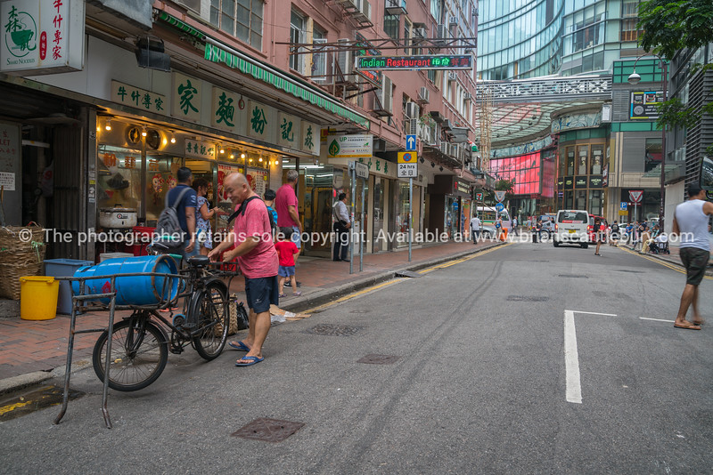 Asian man parke bicycle with large blue gas canister on front in Kowloon street, Kong Kong