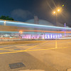 Hong knong  Long exposure captures light trails from passing and turning traffic  in dark night urban street scene