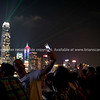 Lights of Hong Kong commercial skyline  defocused bachground to group including selfie taking man holding mobile high.