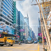 Typically Asian downtown city street  scene with modern buildings on one side bamboo scaffolding