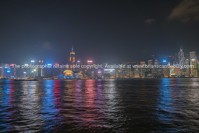 Kong Kong commercial skyline across Victoria Harbor from Kowloon brightly illuminated and colored.