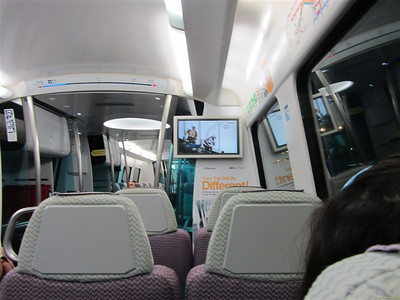 Inside the Airport Express train. Notice the program on TV: ice hockey from NHL. At the ceiling there is a convenient bar showing the progress of the trip.