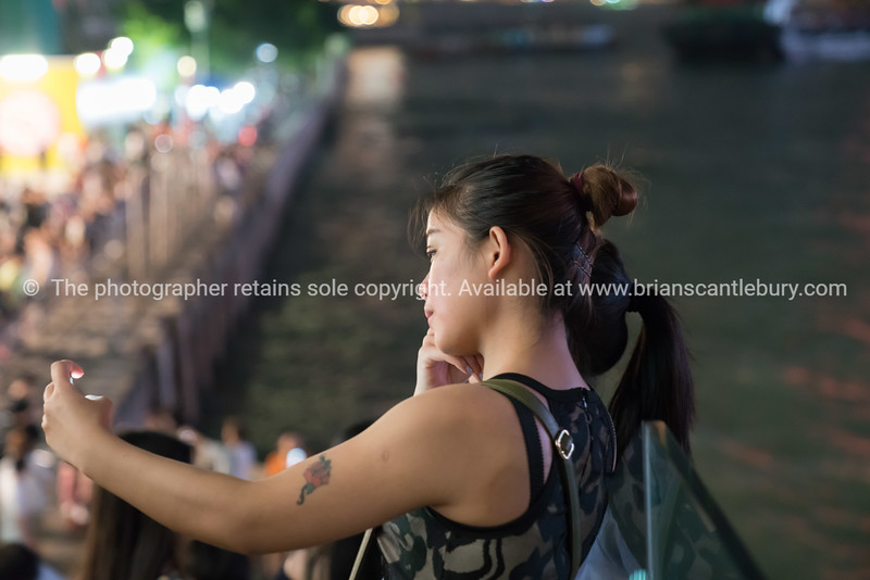 Candid grainy night image young woman face illuminated by light from mobile phone held in front taking selfie