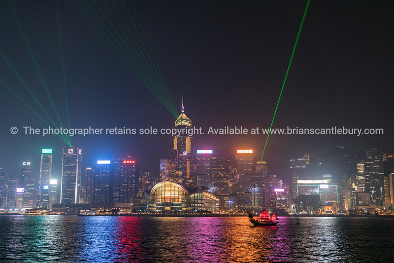 Lights of Hong Kong commercial skyline reflected on calm water of Victoria Harbor.