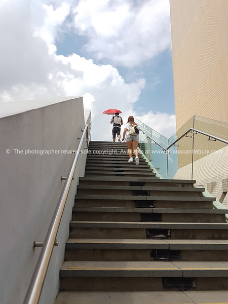 Man with red umbrella of steps leading woman with backpack climbing to top.