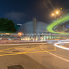 Long exposure captures light trails from passing and turning traffic  in dark night urban street scene