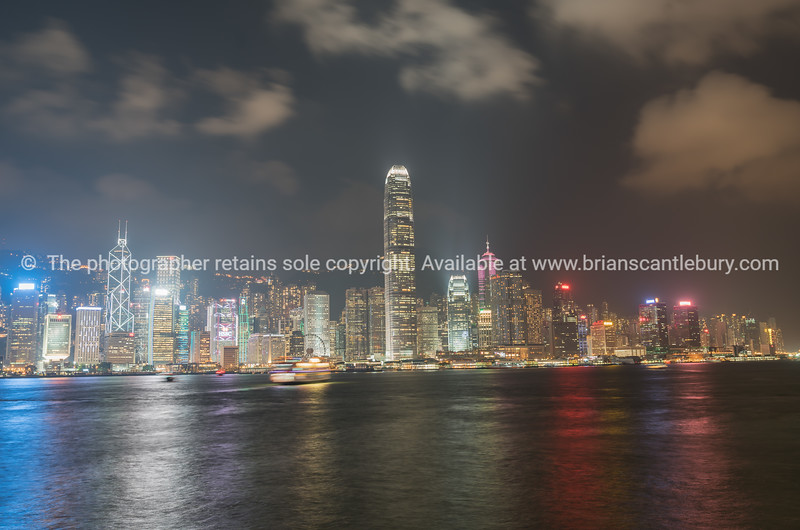 Light cloud drifts across dark sky above illuminated commercial skyline of Kong Kong Islands brightly lit buildings commercial high-rise.