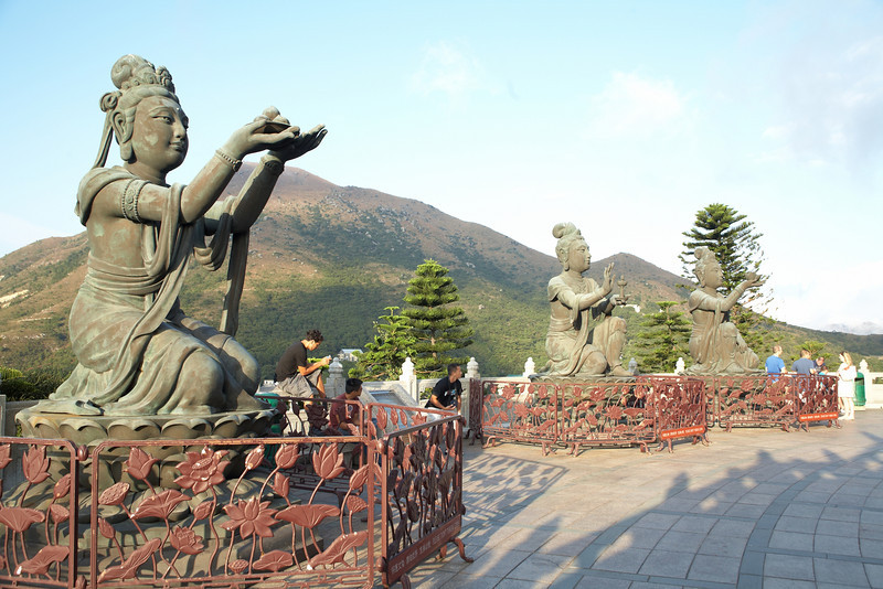 Three of the six devas kneeling below Buddha with their offerings.