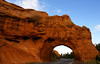The road cuts through an arch in Red Canyon.