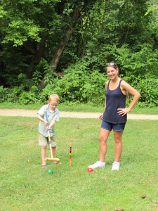 Diane teaching Ethan how to play Croquet.