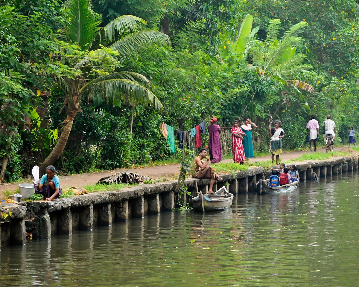 Daily life along a canal in Kerala. Washing, brushing teeth, talking, walking, sending children to school by boat.
