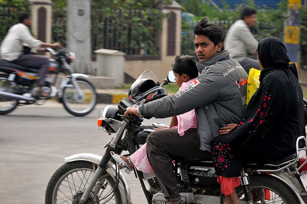 Street scenes. Motorcycles are common in India and there is often more than one person. Notice the fact that no one wears a helmet. (Usually only the driver does. But the helmet is there on the handlebars.) Also notice the ankle bells on the young girl.