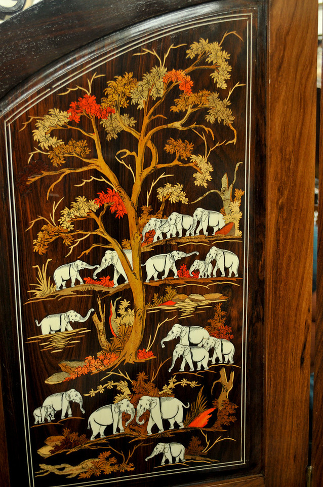 One panel of a screen with inlaid wood designs.