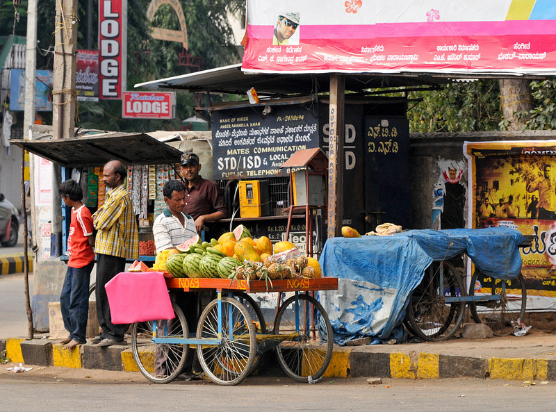 Street scenes. Fruit and vegetable sellers are common throughout India. Notice the telephone is open and available for business.