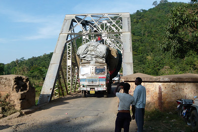"Traveling the roads was a major challenge for our very capable drivers.  The usual one-lane paved roads accommodating traffic of all types -- vehicles, pedestrians, animals -- provided many thrills.  Here a greatly overloaded and obviously unregulated truck blocks traffic as it very gingerly crosses a bridge with great difficulty.  As one guide said, there are three things needed for safe driving in India -- ""A good horn, good brakes, and good luck!"""