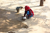 Spreading a mixture of dung and mud to make a fresh floor for the family compound.