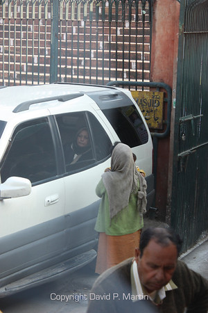 A woman begs for money for her child from a tourist in the car.
