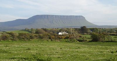 This is the mountain of Ben Bulben, as seen from the north-west side, on the road towards Donegal. On the top of this hill, the mythical hero Dairmud met his death. He was injured by a wild boar, and his former commander Fionn MacCumhall, jealous of his love for Grainne, refused to bring him healing water from the nearby Well of Healing (Heapstown Cairn). Ben Bulben is also famous for the poetry William Butler Yeats wrote for it. The Poet is buried in a churchyard in Drumcliff, north of Sligo town and near the head of the mountain