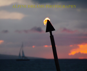 The tiki torch blew intensely as the sun set on a beach in Maui. The sails of a yacht  race to the side of the frame.