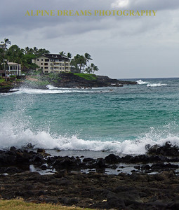 The black lava rocks and cliffs outline the beauty of Poipu beach in Kauai