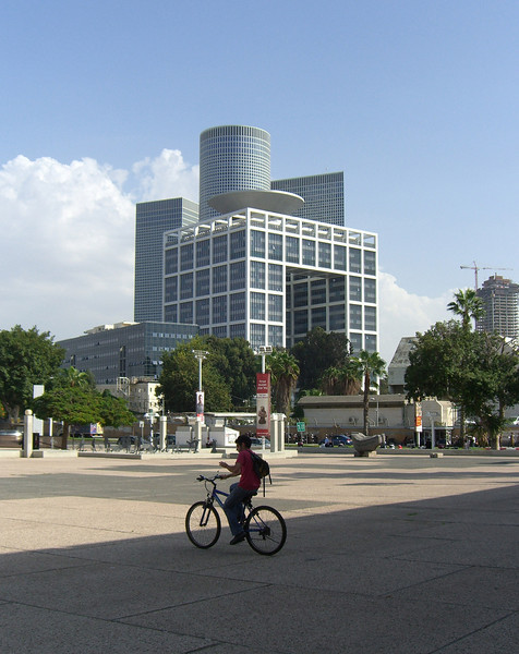 """56-The forecourt of the art museum is directly across Sha'ul HaMelech Blvd from """"HaKirya"""" (IDF HQ). Front: the Matcal Tower (general staff building). Rear: Azrieli Center towers (square tower is 42 floors, round is 49, and triangular is 46 stories)."""