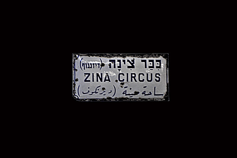 "1-Displayed in the lobby of the Cinema Hotel, this one-time street sign shows the original name of Dizengoff square: In Hebrew, ""Kikar Zina (Dizengoff)"". Six buildings of similar height and form encircled Kikar Dizengoff."